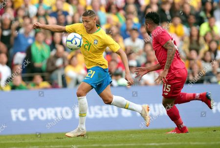Brazil's Richarlison runs with the ball chased by Panama's Eric Davis, right, during the friendly soccer match between Brazil and Panama at the Dragao stadium in Porto, Portugal