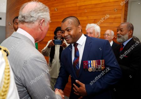 Britain's Prince Charles shaking hands with recipient of the Victoria Cross, Lance Sergeant Johnson Beharry as he tours the Parliament during a visit to Grenada