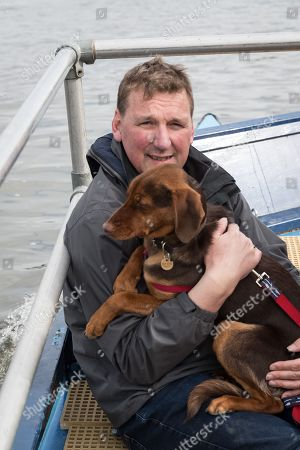 23 March 2019. Boat Race Fixture.  OUWBC vs Molesey BC., Pictured:- Umpire Sir Matthew Pinsent CBE aboard the Umpire's launch with his dog., As preparation for the The Boat Races, Oxford and Cambridge clubs participate in a number of Fixtures against other clubs, rowing the same Tideway course as used for the Boat Race., OUWBC Crew List (Yellow hulled boat):-, Stroke: Amelia Standing, 7. Tina Christmann, 6. Beth Bridgman, 5. Liv Pryer, 4. Lizzie Polgreen, 3. Renée Koolschijn, 2. Anna Murgatroyd, Bow. Issy Dodds, Cox. Eleanor Shearer
