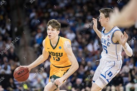 Stock Photo of Chris Quayle, Alex O'Connell. North Dakota State guard Chris Quayle (13) dribbles around Duke guard Alex O'Connell (15) during the second half of a first-round game in the NCAA men's college basketball tournament, in Columbia, S.C. Duke defeated North Dakota State 85-62
