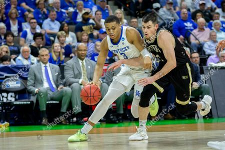 Kentucky guard Keldon Johnson (3) dribbles the ball against Wofford guard Fletcher Magee, right, during the second half of the second round men's college basketball game in the NCAA Tournament, in Jacksonville, Fla