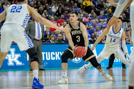 Wofford guard Fletcher Magee (3) looks to pass the ball against the Wofford defense during the first half of the second round men's college basketball game in the NCAA Tournament, in Jacksonville, Fla