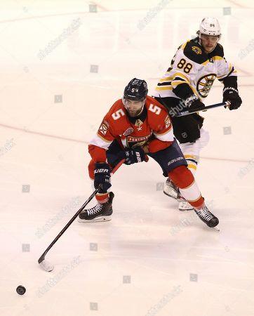 Florida Panthers' Aaron Ekblad (5) reaches for the puck as Boston Bruins' David Pastrnak (88) defends during the second period of an NHL hockey game, in Sunrise, Fla