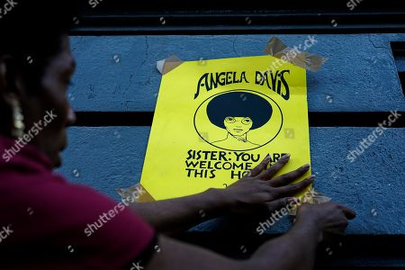 A woman tapes to a wall a poster featuring American political activist Angela Davis before the start of an open air rally in front of the University of the Republic in Montevideo, Uruguay, . Davis received an Honoris Causa Doctorate degree from the Uruguayan university
