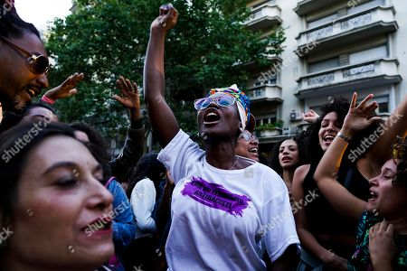 """A woman wearing a T-shirt with a message that reads in Spanish: """"For an anti-racist feminism,"""" cheers during an open air rally in front of the University of the Republic, where American political activist Angela Davis spoke, in Montevideo, Uruguay, . Davis received an Honoris Causa Doctorate degree from the Uruguayan university"""