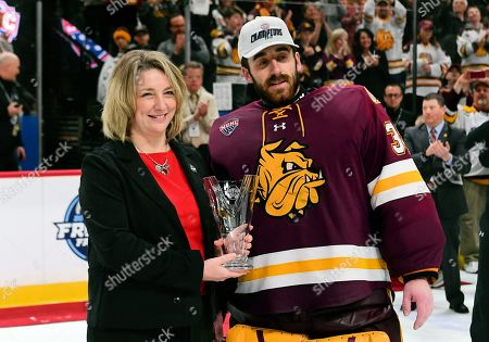 Stock Picture of Heather Weems presents Minnesota-Duluth Bulldogs goaltender Hunter Shepard (32) with the Most Valuable Player award after the Minnesota Duluth Bulldogs defeated the St. Cloud State Huskies 3-2 in double overtime to win the NCHC Frozen Faceoff championship at the Xcel Energy Center, St. Paul, MN