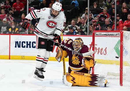 St. Cloud State Huskies forward Blake Lizotte (27) jumps to get out of the way of a shot on Minnesota-Duluth Bulldogs goaltender Hunter Shepard (32) during the NCHC Frozen Faceoff championship between the Minnesota Duluth Bulldogs and the St. Cloud State Huskies at the Xcel Energy Center, St. Paul, MN