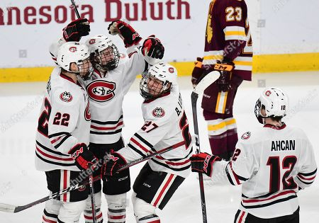 St. Cloud State players congratulate St. Cloud State Huskies forward Patrick Newell (14) after he scored during the NCHC Frozen Faceoff championship between the Minnesota Duluth Bulldogs and the St. Cloud State Huskies at the Xcel Energy Center, St. Paul, MN. Duluth defeated St. Cloud State 3-2 in double overtime