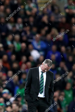 Northern Ireland manager Michael O'Neill dips his head in a show of dejection
