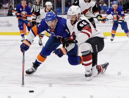 New York Islanders' Andrew Ladd, left, fights for control of the puck with Arizona Coyotes' Jason Demers (55) during the second period of an NHL hockey game, in Uniondale, N.Y