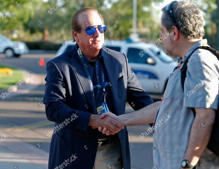 Los Angeles Chargers owner Dean Spanos, left, is greeted as he arrives for the annual NFL owners meetings, in Phoenix