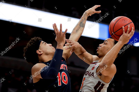 Virginia Tech guard Justin Robinson, right, shoots over Liberty guard Elijah Cuffee during the first half of a second-round game in the NCAA men's college basketball tournament, in San Jose, Calif