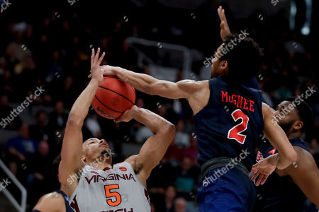 Liberty guard Darius McGhee (2) blocks a shot by Virginia Tech guard Justin Robinson (5) during the first half of a second-round game in the NCAA men's college basketball tournament, in San Jose, Calif