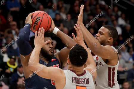 Liberty forward Myo Baxter-Bell, left, is guarded by Virginia Tech guard Justin Robinson (5) and forward P.J. Horne during the first half of a second-round game in the NCAA men's college basketball tournament, in San Jose, Calif
