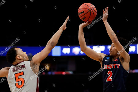 Liberty guard Darius McGhee, right, shoots over Virginia Tech guard Justin Robinson during the second half of a second-round game in the NCAA men's college basketball tournament, in San Jose, Calif