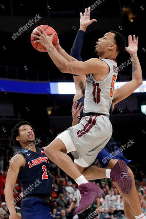 Virginia Tech guard Justin Robinson drives to the basket past Liberty guards Darius McGhee (2) and Elijah Cuffee during the second half of a second-round game in the NCAA men's college basketball tournament, in San Jose, Calif