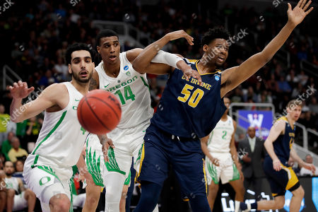 Oregon guard Ehab Amin, left, and forward Kenny Wooten (14) and UC Irvine forward Elston Jones (50) try for a rebound during the second half of a second-round game in the NCAA men's college basketball tournament, in San Jose, Calif