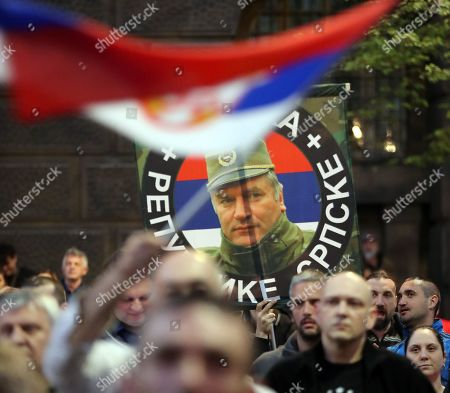 Citizens of Belgrade wave Serbian national flags, carry banners with anti-NATO slogans, crossed European Union emblems, photographs of Russian President Vladimir Putin and the Commander of the Army of Republika Srpska Ratko Mladic at a gathering outside the General Staff building, after which they walked through the streets of Belgrade to the Russian Embassy, marking the 20th anniversary of the North Atlantic Treaty Organization (NATO) bombing of Yugoslavia; in Belgrade, Serbia, 24  March 2019. The NATO bombing of the Federal Republic Yugoslavia began 20 years ago in which, according to unofficial sources, about 2,500 civilians and about 1,000 soldiers and police officers died in 11 weeks. In the 78-day bombardment, infrastructure, businesses, health facilities, media outlets and military facilities were badly damaged. The NATO action came after unsuccessful negotiations on a solution to the Kosovo crisis in Rambouillet and Paris, February and March 1999. The bombing of Yugoslavia ended on 10 June, with the adoption of UN Security Council Resolution 1244, followed by the withdrawal of the army and police from the province and the entry of international military troops.
