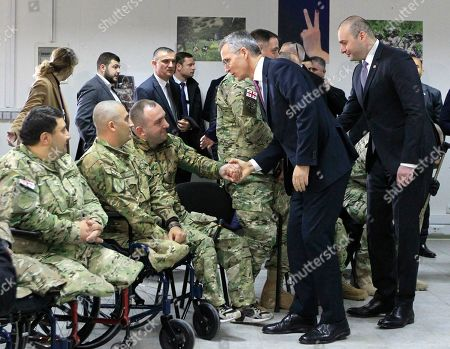 NATO Secretary General Jens Stoltenberg and Georgian Prime Minister Mamuka Bakhtadze, right, meet with veterans of Georgian army during multinational military exercises NATO - Georgia Exercise 2019, at the NATO-Georgia Joint Training and Evaluation Center in Krtsanisi, just outside Tbilisi, Georgia
