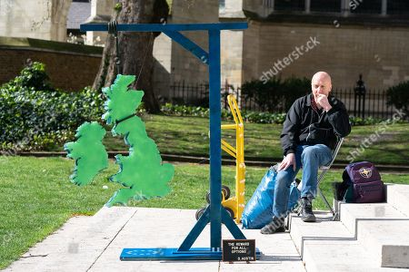 A sculpture depicting a model of the United Kingdom hangs from gallows as part of a Brexit demonstration in Westminster