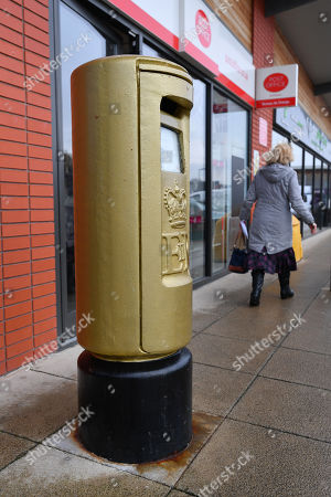 Stock Photo of Gold Royal Mail Postbox In Disgraced Cyclist Bradley Wiggins Home Town Of Eccleston Lancs. Which Was Painted Gold In Honour Of His Olympic Gold Medal Win.
