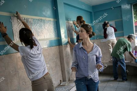 Stock Photo of Bridesmaid Stefania Fernandez, who is former Miss Universe 2009, center, helps stencil a wall at a children's hospital, as part of activities for the wedding of Maria Fernanda Vera and Juan Jose Pocaterra, in Acarigua, Venezuela. About 50 wedding guests joined the couple to paint the rundown hospital's blue walls, organized with the help of Venezuelan NGO Tracing Public Spaces. The bride regularly contributes powdered milk and other supplies to the hospital