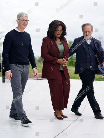 From left, Apple CEO Tim Cook, Oprah Winfrey and Steven Spielberg walk together outside the Steve Jobs Theater as they prepare to pose for photos during an event to announce new Apple products, in Cupertino, Calif