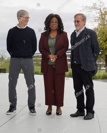 Apple CEO Tim Cook, Oprah Winfrey and Steven Spielberg pose for a photo outside the Steve Jobs Theater during an event to announce new Apple products, in Cupertino, Calif