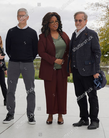 Apple CEO Tim Cook, Oprah Winfrey, and Steven Spielberg poses for a photo outside the Steve Jobs Theater after an event to announce new Apple products, in Cupertino, Calif