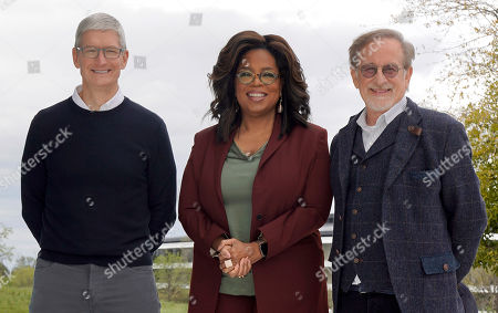 From left, Apple CEO Tim Cook, Oprah Winfrey and Steven Spielberg pose for a photo outside the Steve Jobs Theater after an event to announce new Apple products, in Cupertino, Calif