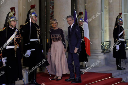 French luxury group Chairman and CEO Bernard Arnault, right, his wife Helene Mercier arrive for a state dinner at the Elysee Palace in Paris, France, . Chinese President Xi Jinping is on a 3-day state visit in France where he is expected to sign a series of bilateral and economic deals on energy, the food industry, transport and other sectors