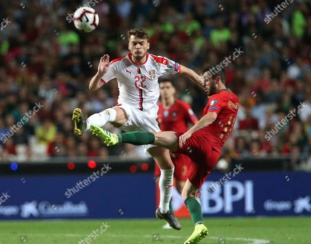 Serbia's Adem Ljajic, left, and Portugal's Bernardo Silva challenge for the ball during the Euro 2020 group B qualifying soccer match between Portugal and Serbia at the Luz stadium in Lisbon, Portugal