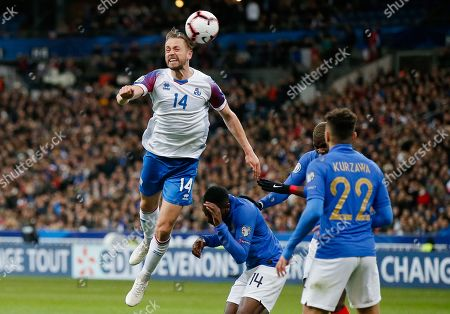 Iceland's Kari Arnason heads a ball during the Euro 2020 group H qualifying soccer match between France and Iceland at Stade de France stadium in Saint Denis, outside Paris, France