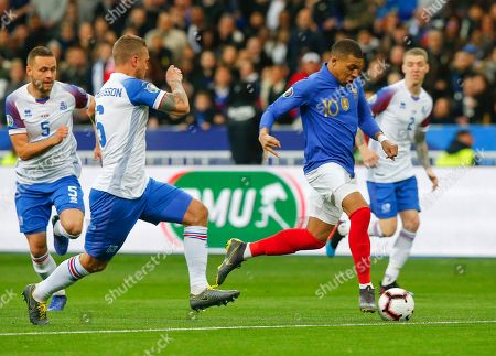 France's Kylian Mbappe, right, challenges for the ball with Iceland's Ragnar Sigurdsson during the Euro 2020 group H qualifying soccer match between France and Iceland at Stade de France stadium in Saint Denis, outside Paris, France