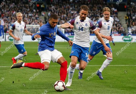 France's Kylian Mbappe, left, passes the ball for the opening goal next to Iceland's Kari Arnason during the Euro 2020 group H qualifying soccer match between France and Iceland at Stade de France stadium in Saint Denis, outside Paris, France
