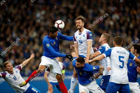 France's Raphael Varane, center left, jumps for the ball with Iceland's Kari Arnason during the Euro 2020 group H qualifying soccer match between France and Iceland at the Stade de France in Saint Denis, north of Paris