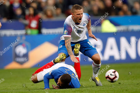 France's Kylian Mbappe falls after a tackle by Iceland's Ragnar Sigurdsson during the Euro 2020 group H qualifying soccer match between France and Iceland at the Stade de France in Saint Denis, north of Paris