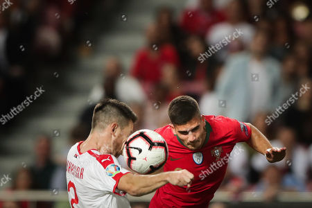 Portugal's Andre Silva (R) fights for the ball with Serbia's Antonio Rukavina during the UEFA EURO 2020 Group B qualifying soccer match between Portugal and Serbia, at Luz Stadium, Lisbon, Portugal, 25 March 2019.