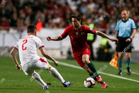 Portugal's Raphael Guerreiro (R) fights for the ball with Serbia's Antonio Rukavina during the UEFA EURO 2020 Group B qualifying soccer match between Portugal and Serbia, at Luz Stadium, Lisbon, Portugal, 25 March 2019.
