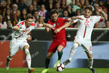 Portugal's Bernardo Silva (C) fight for the ball with Serbia's Filip Mladenovic (L) and Adem Ljajic (D) during the UEFA EURO 2020 Group B qualifying soccer match between Portugal and Serbia, at Luz Stadium, Lisbon, Portugal, 25 March 2019.