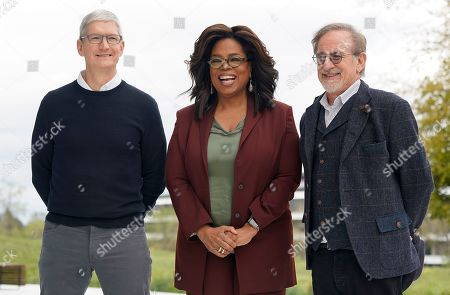 From left, Apple CEO Tim Cook, Oprah Winfrey and Steven Spielberg pose for a photo outside the Steve Jobs Theater during an event to announce new Apple products, in Cupertino, Calif