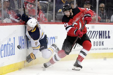 Buffalo Sabres defenseman Casey Nelson (8) hits the boards while competing for the puck with New Jersey Devils right wing Drew Stafford (18) during the second period of an NHL hockey game, in Newark, N.J