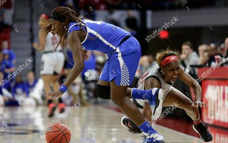 Stock Image of North Carolina State's Kiara Leslie falls while Kentucky's Rhyne Howard dribbles during the first half of a second round women's college basketball game in the NCAA Tournament in Raleigh, N.C