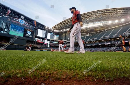 Arizona Diamondbacks' Steven Souza Jr. walks on new turf at the team's home field before a spring training baseball game against the Chicago White Sox, in Phoenix, Ariz. The synthetic grass at Chase Field is designed specifically for baseball. The team previously played on grass there