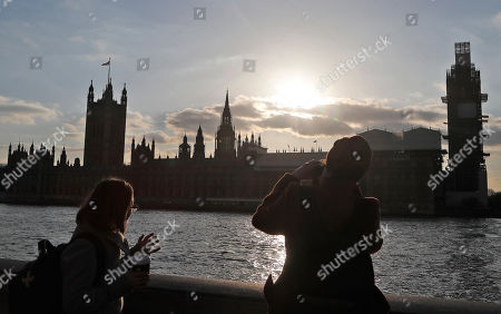 Tourists take photographs as the sun sets behind the Houses of Parliament in London, . British Prime Minister Theresa May's government says Parliament's decision to take control of the stalled process of leaving the European Union underscores the need for lawmakers to approve her twice-defeated Brexit deal