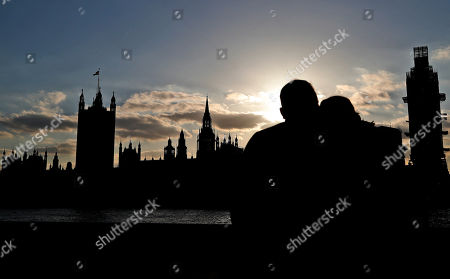 A couple enjoys the sunset behind the Houses of Parliament in London, . British Prime Minister Theresa May's government says Parliament's decision to take control of the stalled process of leaving the European Union underscores the need for lawmakers to approve her twice-defeated Brexit deal