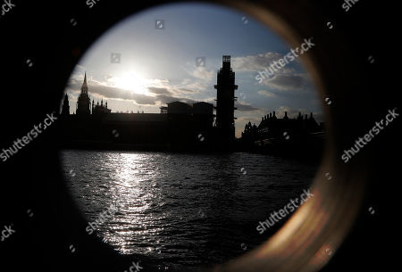 The Houses of Parliament, left, with Big Ben's clock tower, centre, that is covered in scaffolding for renovations, are seen through the hole of a binoculars stand in London, . British Prime Minister Theresa May's government says Parliament's decision to take control of the stalled process of leaving the European Union underscores the need for lawmakers to approve her twice-defeated Brexit deal