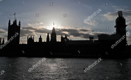 The sun sets behind the Houses of Parliament in London, . British Prime Minister Theresa May's government says Parliament's decision to take control of the stalled process of leaving the European Union underscores the need for lawmakers to approve her twice-defeated Brexit deal