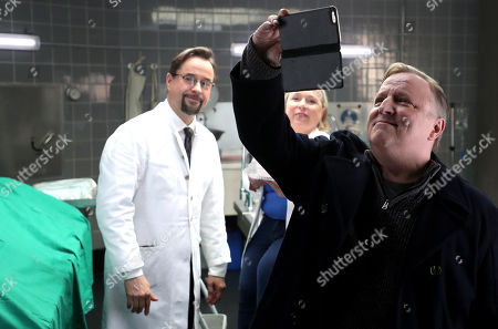 Stock Picture of Axel Prahl (R), who plays the role of police inspector Frank Thiel, German actor Jan Josef Liefers (L), who plays the role of Forensic Professor Dr. Karl-Friedrich Boerne and German actress Christine Urspruch (R), who plays the role of specialist in forensic medicine Dr. Silke Alberich Haller pose during a photo call in Cologne, Germany, 26 March 2018.