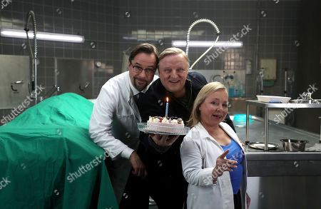 Axel Prahl (C), who plays the role of police inspector Frank Thiel, German actor Jan Josef Liefers (L), who plays the role of Forensic Professor Dr. Karl-Friedrich Boerne and German actress Christine Urspruch (R), who plays the role of specialist in forensic medicine Dr. Silke Alberich Haller pose during a photo call in Cologne, Germany, 26 March 2018.